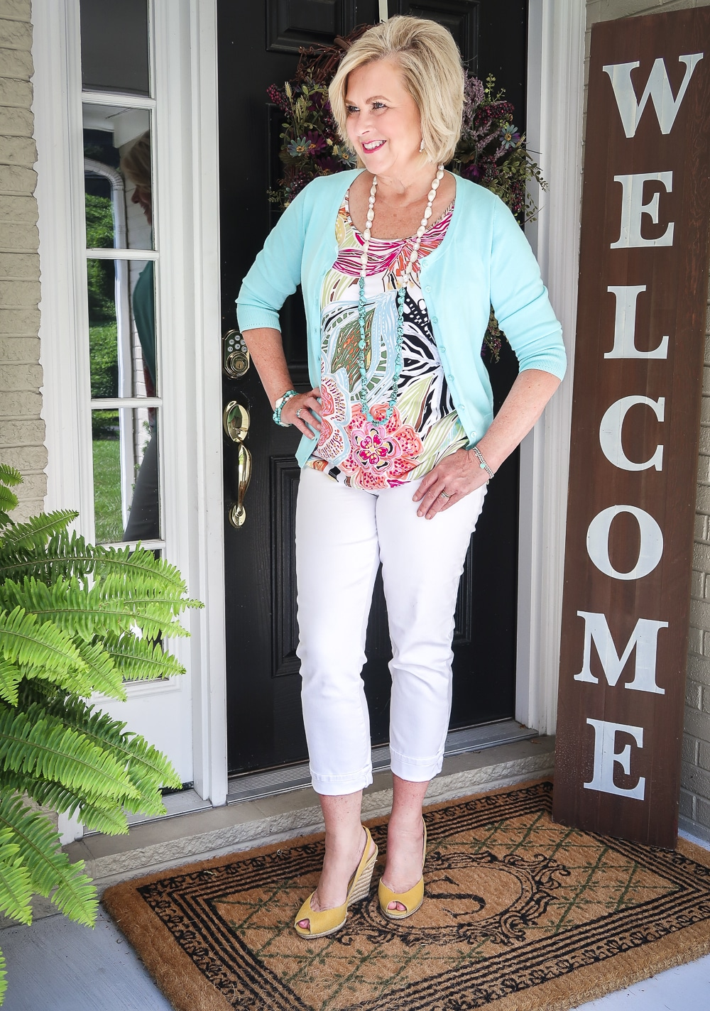 Fashion Blogger 50 Is Not Old is wearing an aqua cardigan, a bright tropical top, white ankle jeans, and yellow espadrilles