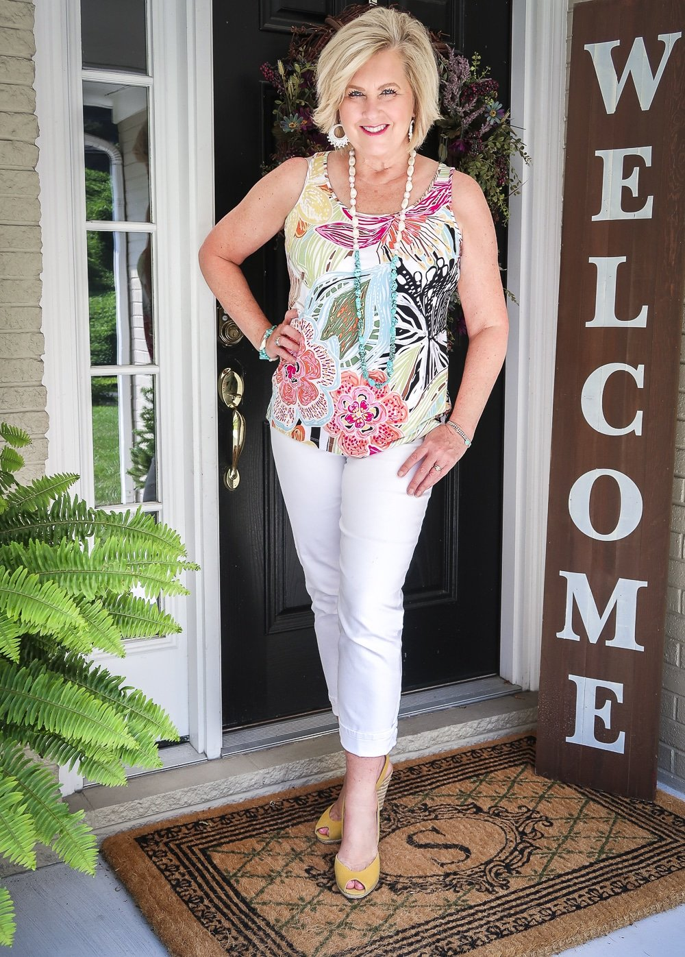 Fashion Blogger 50 Is Not Old is looking summery in a bright tropical top, white ankle jeans, and yellow espadrilles