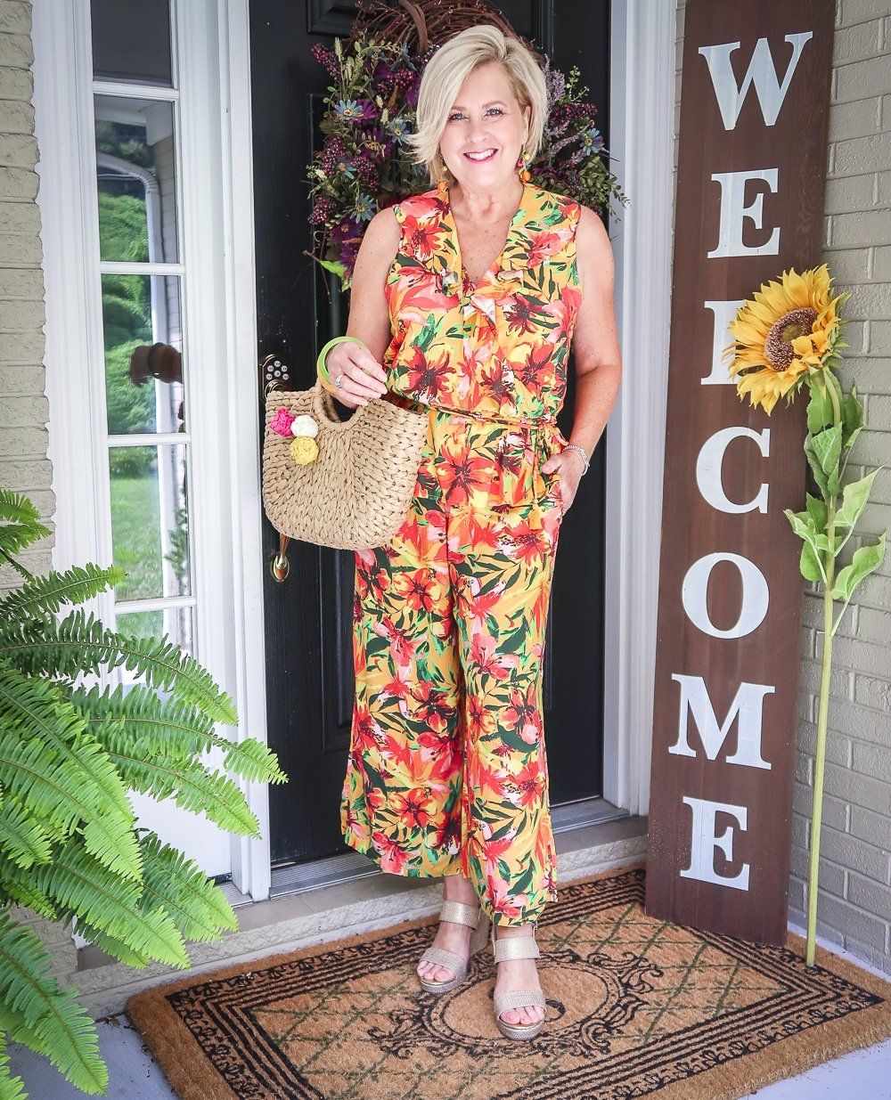 Fashion Blogger 50 Is Not Old is wearing a tropical ruffled peplum top, and a matching pant with gold espadrille wedges and a straw bag