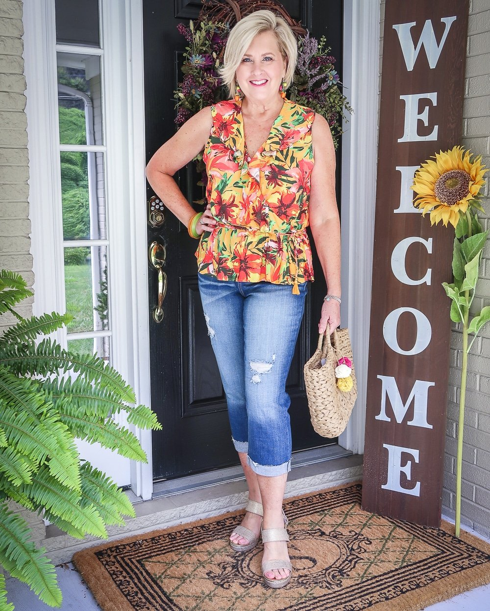 Fashion Blogger 50 Is Not Old is wearing a tropical ruffled peplum top, and a pair of distressed crop jeans, with gold espadrille wedges and a straw bag