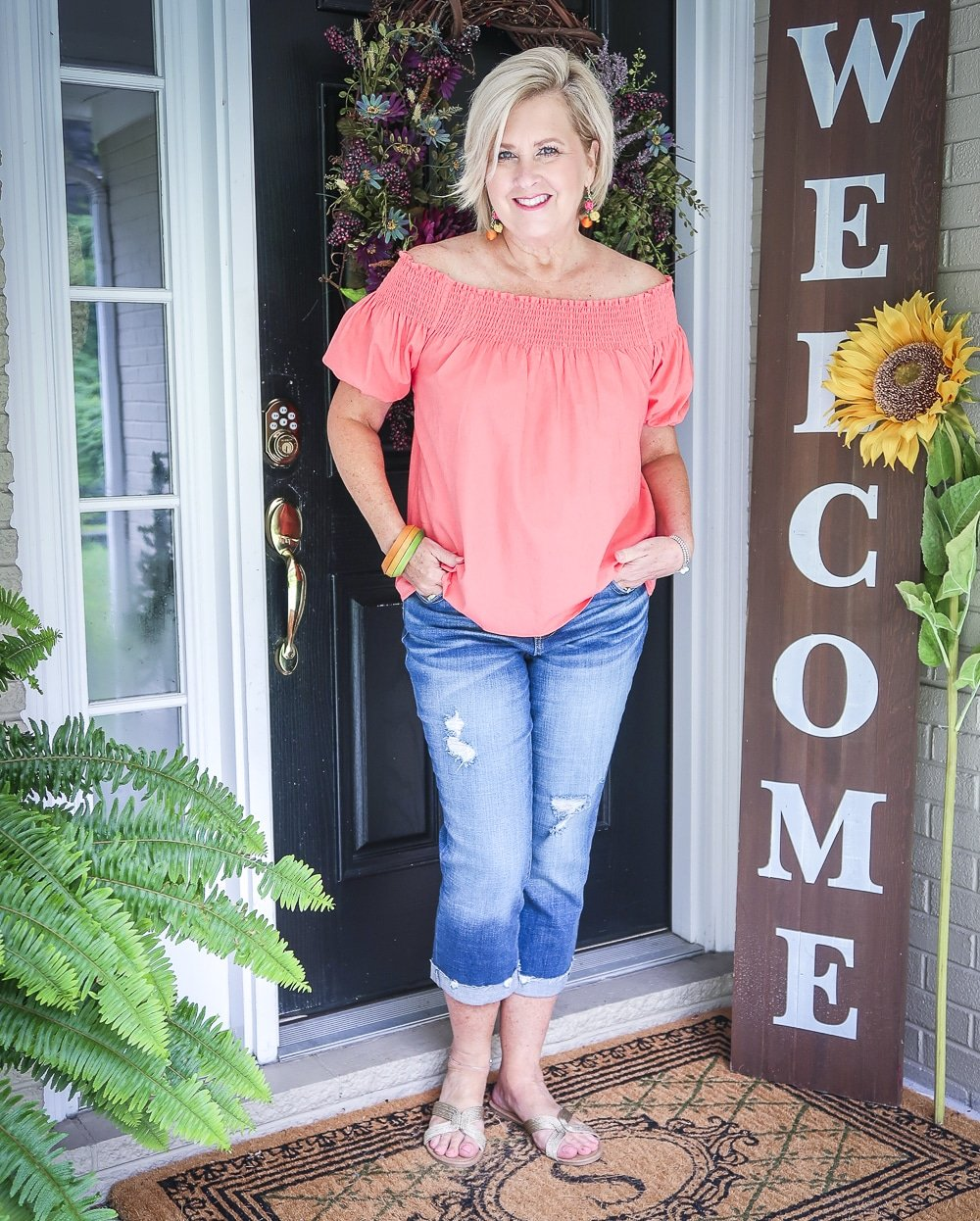 Fashion Blogger 50 Is Not Old is wearing a off the shoulder coral top with distressed crop jeans, with gold espadrille wedges and a straw bag