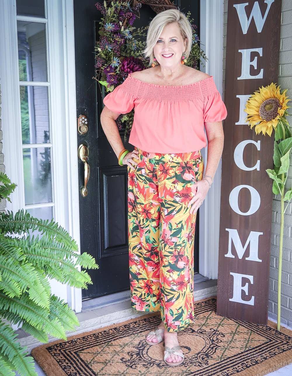 Fashion Blogger 50 Is Not Old is wearing a off the shoulder coral blouse with a tropical printed crop pant with gold flats