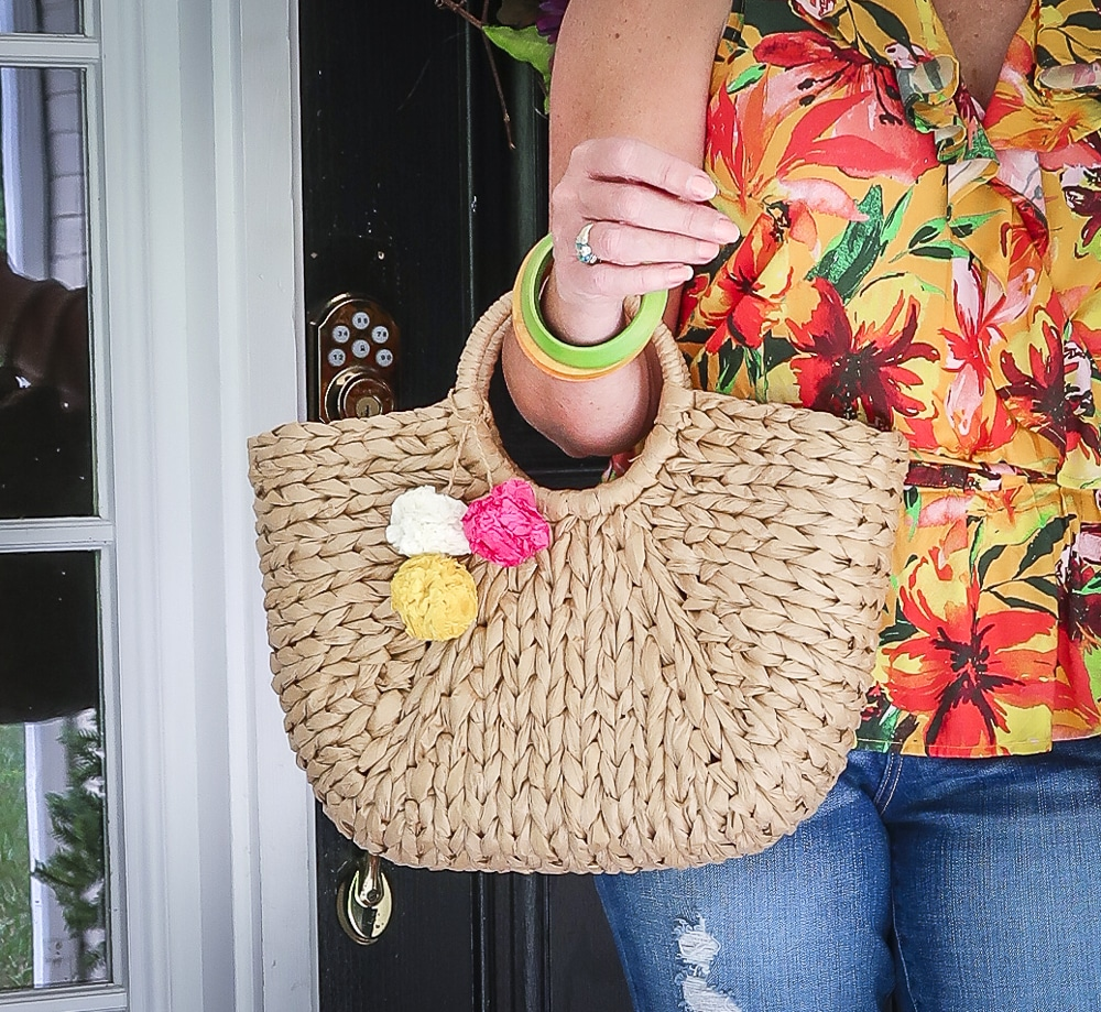 Fashion Blogger 50 Is Not Old is carrying a straw bag with bright pompoms from Walmart