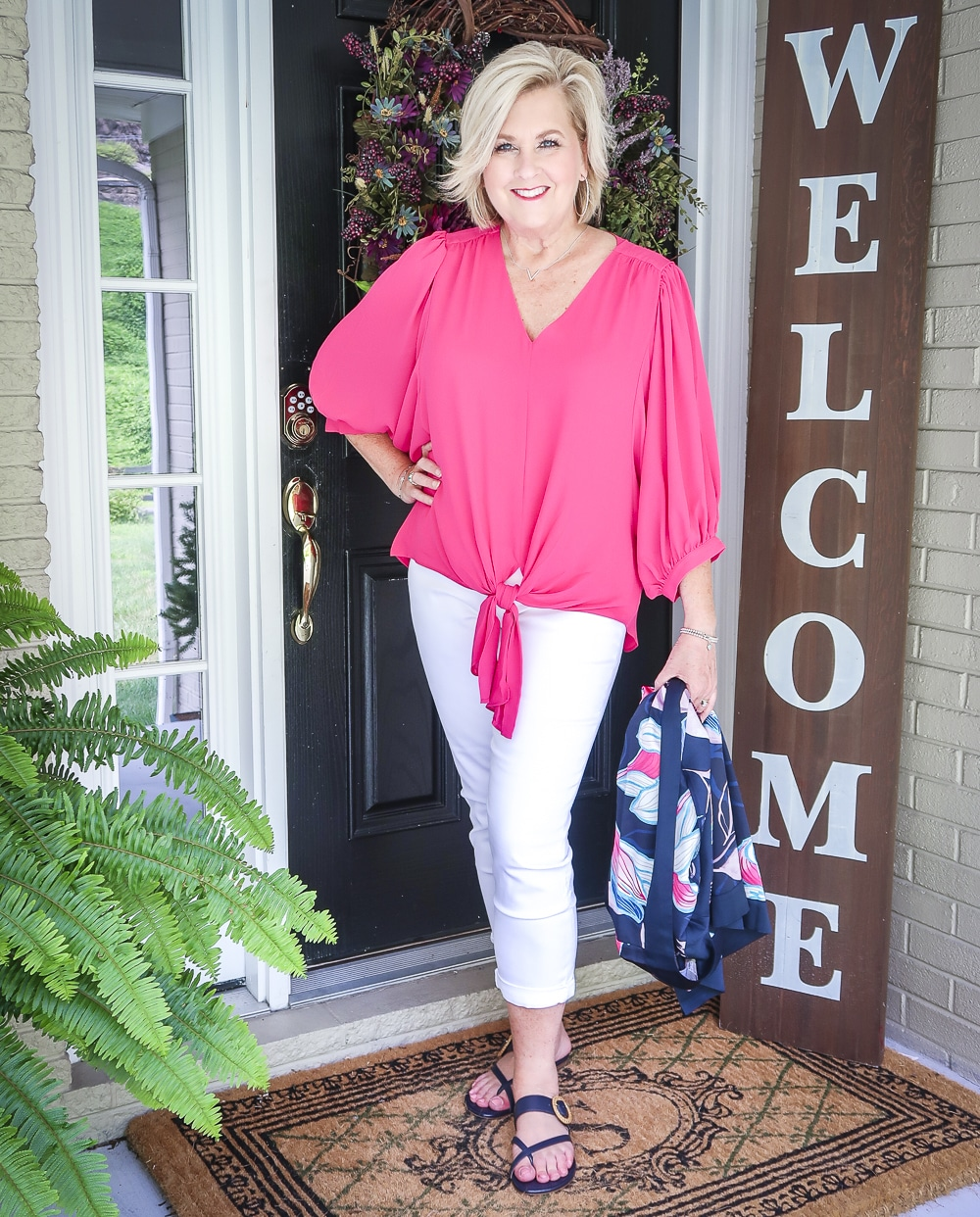 Fashion Blogger 50 Is Not Old is bright and colorful in a tie-front pink blouse, white girlfriend crop jeans, and navy sandals