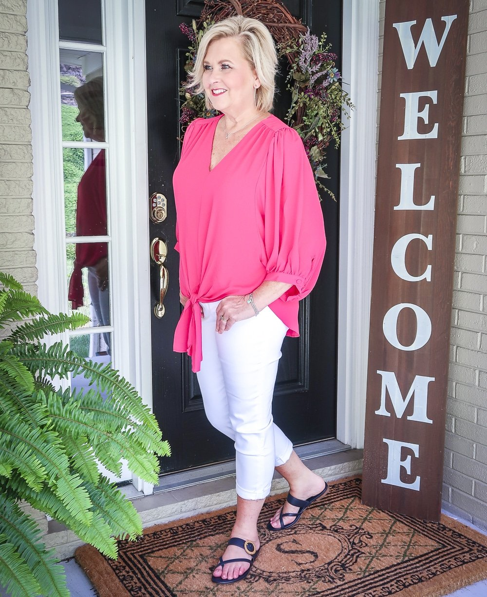 Fashion Blogger 50 Is Not Old is bright and colorful in a tie-front pink blouse and white girlfriend crop jeans