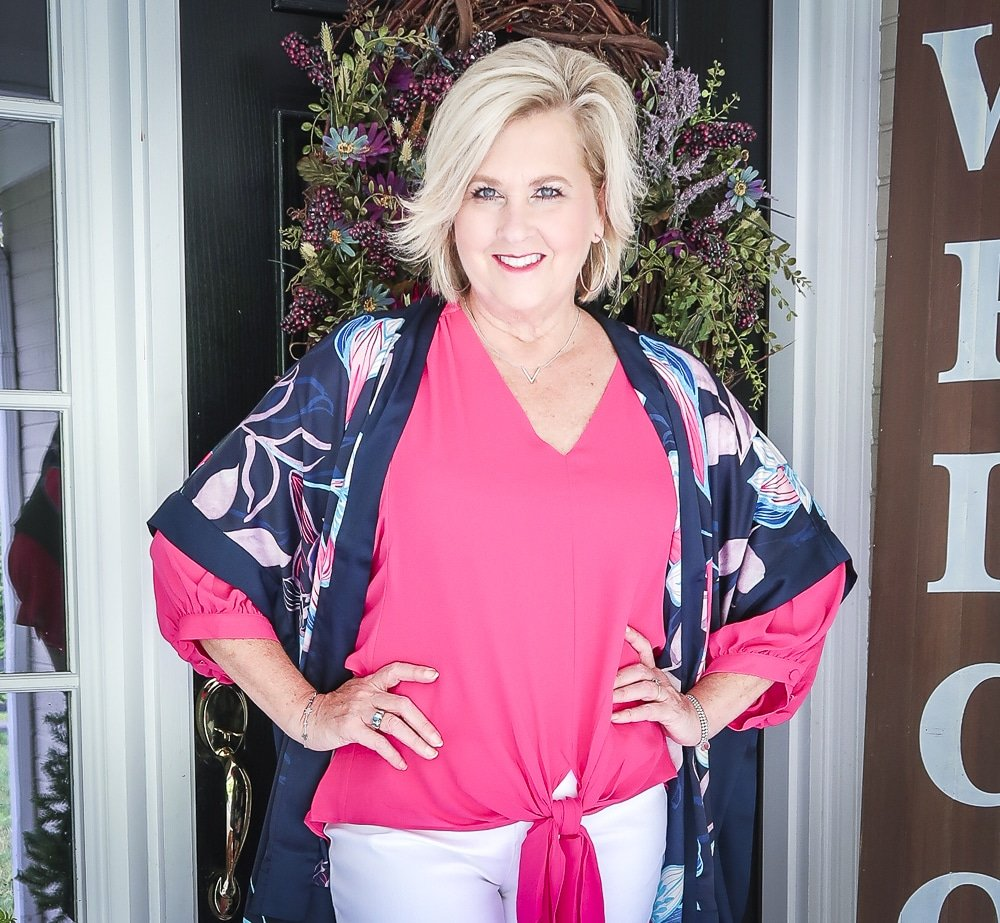 Fashion Blogger 50 Is Not Old is bright and colorful in a tie-front pink blouse and a beautiful floral navy ruana