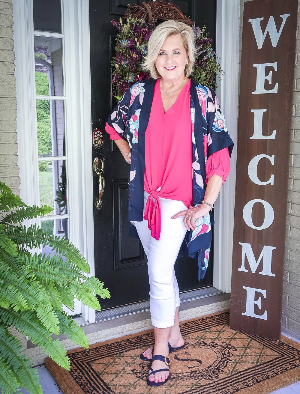 Fashion Blogger 50 Is Not Old is bright and colorful in a tie-front pink blouse, white girlfriend crop jeans, floral navy ruana from Chicos, and navy sandals