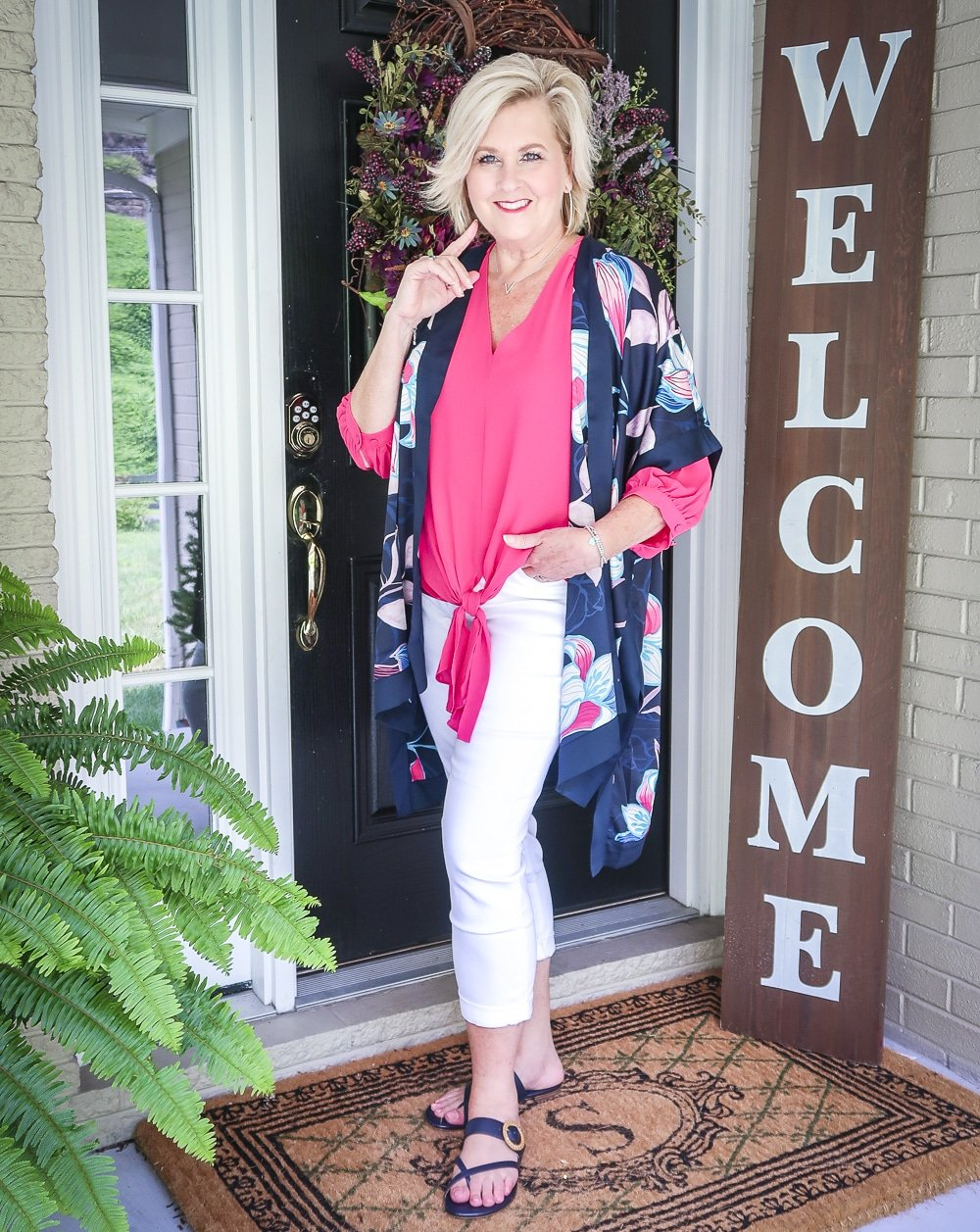 Fashion Blogger 50 Is Not Old is bright and colorful in a tie-front pink blouse, white girlfriend crop jeans, floral ruana, and navy sandals