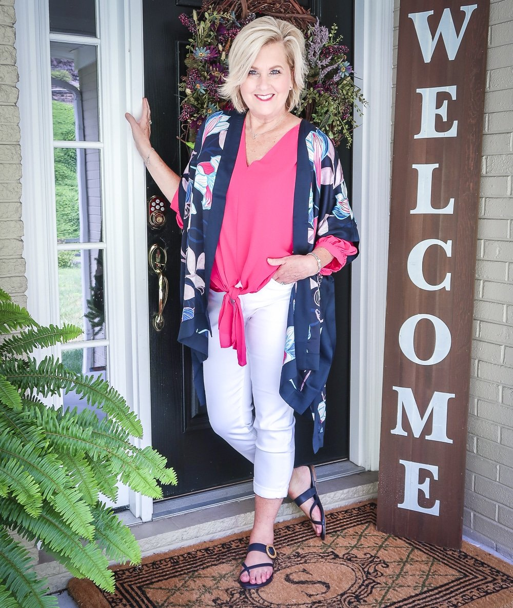 Fashion Blogger 50 Is Not Old is bright and colorful in a tie-front pink blouse, white girlfriend crop jeans, floral navy ruana, and navy sandals