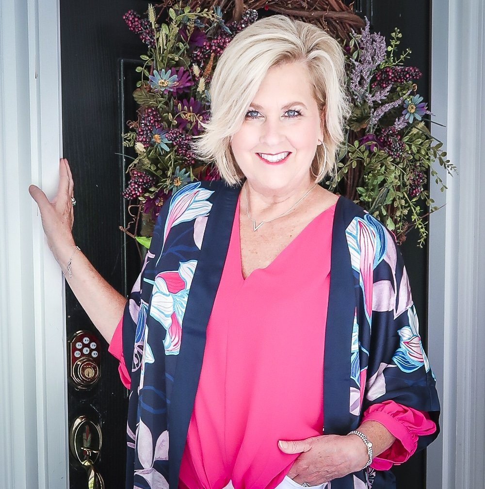 Fashion Blogger 50 Is Not Old is bright and colorful in a tie-front pink blouse with silver jewelry