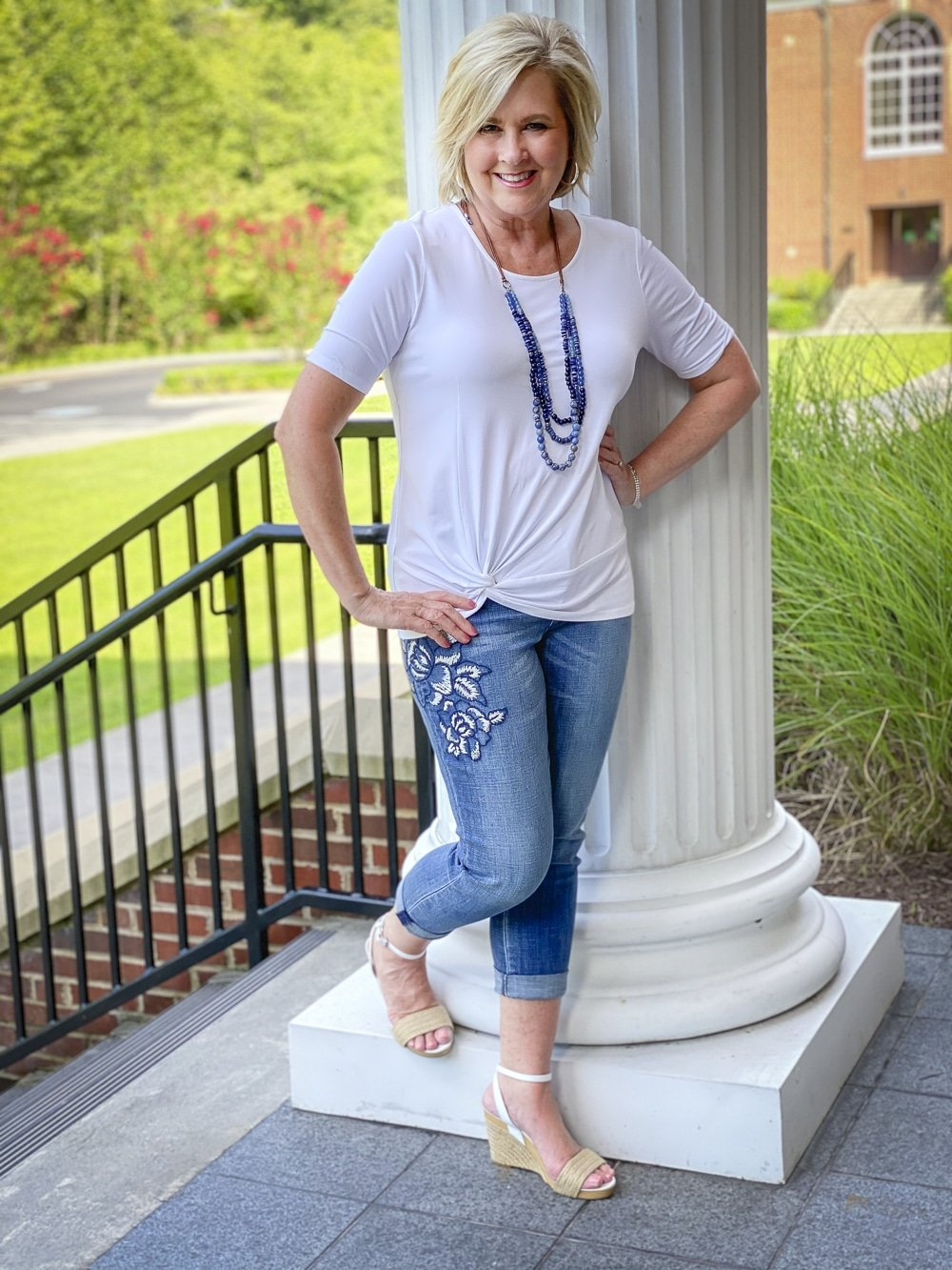 Fashion Blogger 50 Is Not Old is wearing a white twist top, embroidered jeans, and blue beaded jewelry