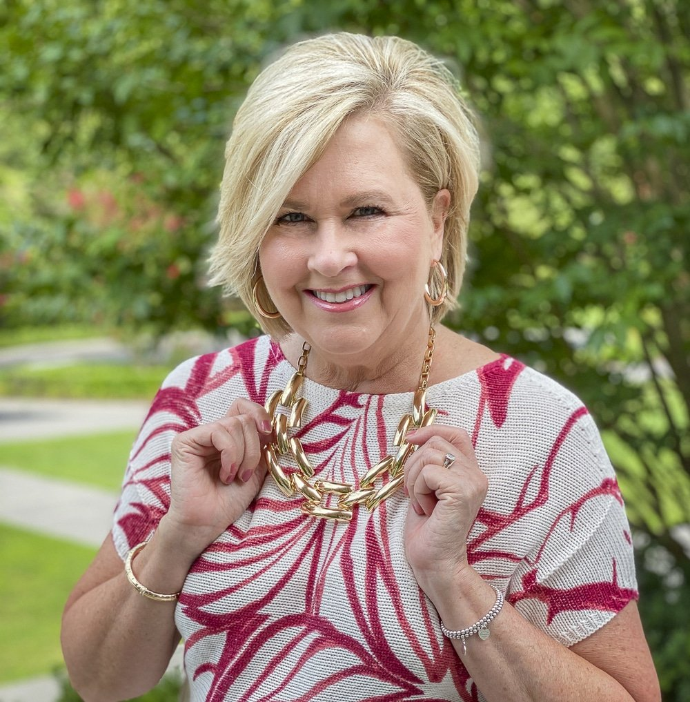 Fashion Blogger 50 Is Not Old is wearing a red and white tropical leaf print sweater and goldtone jewelry