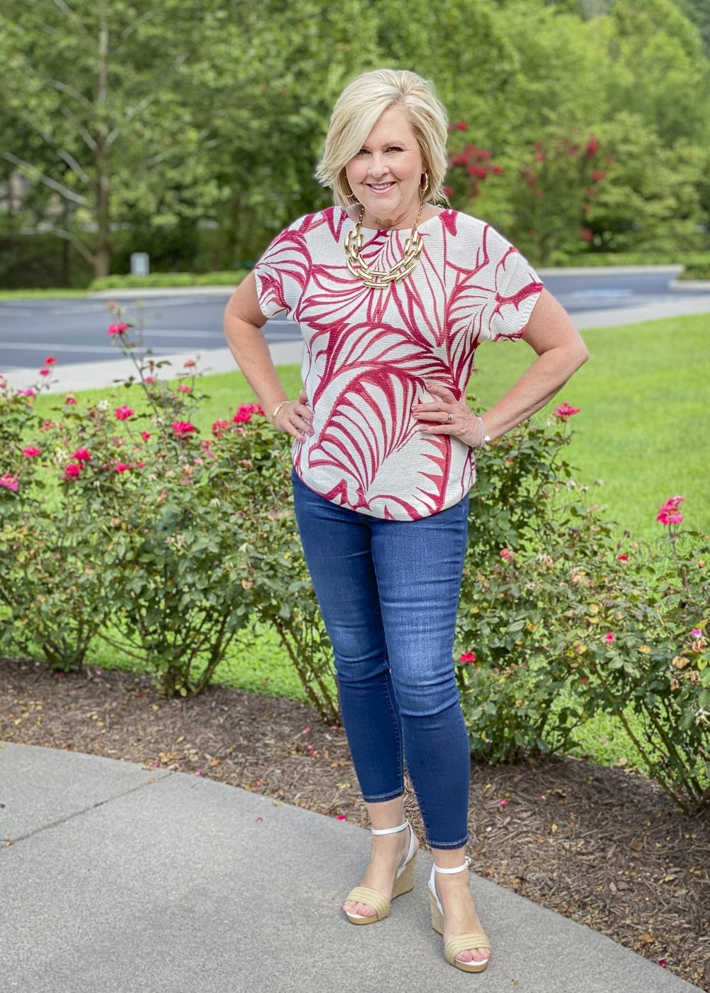 Fashion Blogger 50 Is Not Old is surrounded by red roses in her red and white tropical leaf print sweater and skinny ankle jeans from Chico's