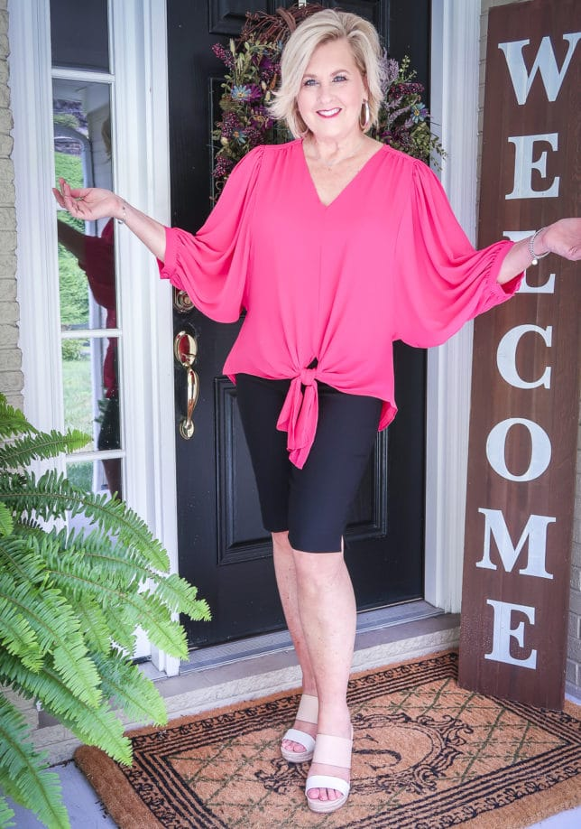Fashion Blogger 50 Is Not Old is wearing a pink front-tie blouse and black Bermuda shorts