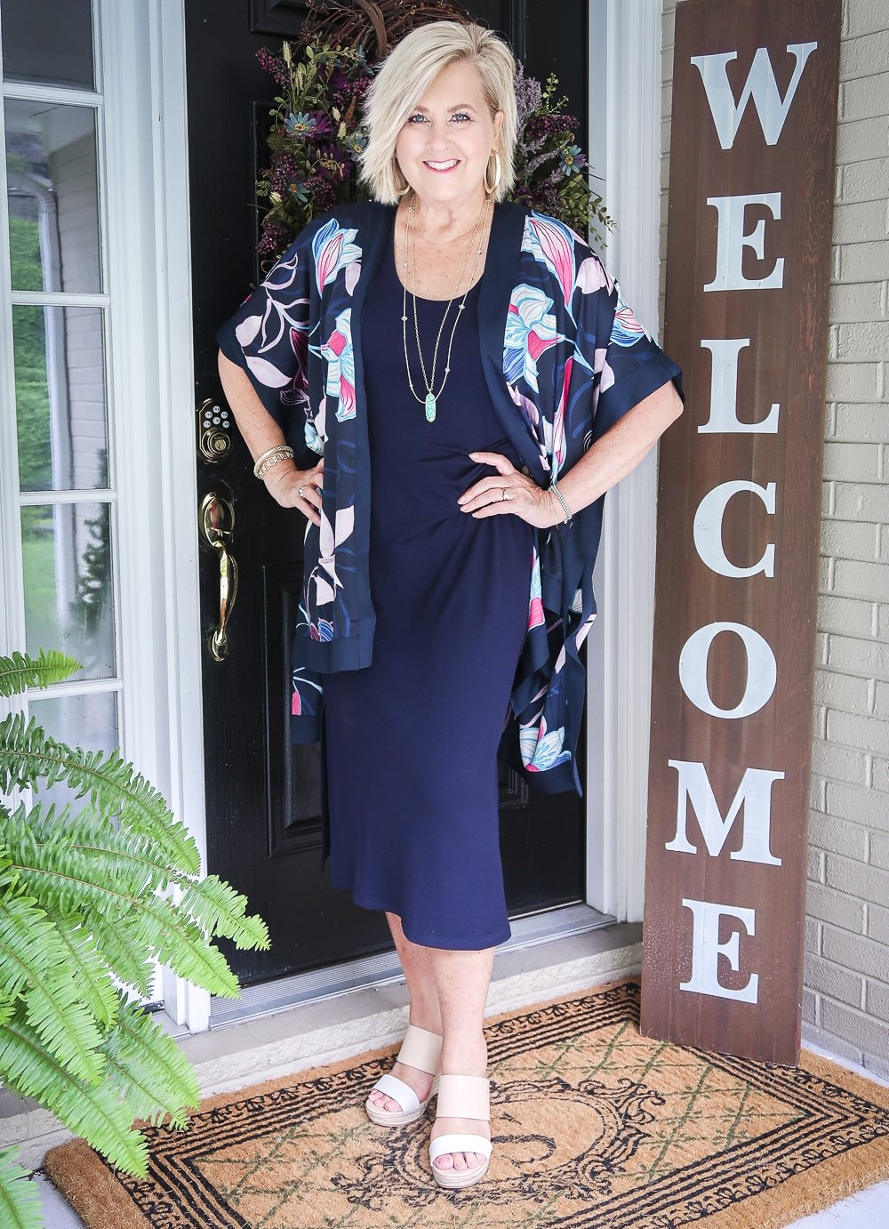 Fashion Blogger 50 Is Not Old is wearing a navy midi dress in all of the seasons. In summer, she added a floral kimono, and two-tone espadrille wedge shoes