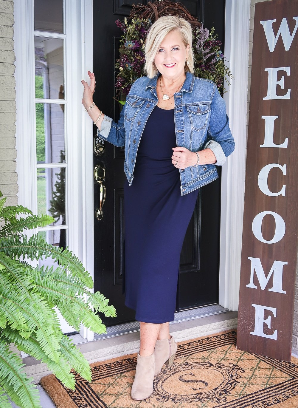 Fashion Blogger 50 Is Not Old in a denim Jacket, a navy midi dress, and ankle boots