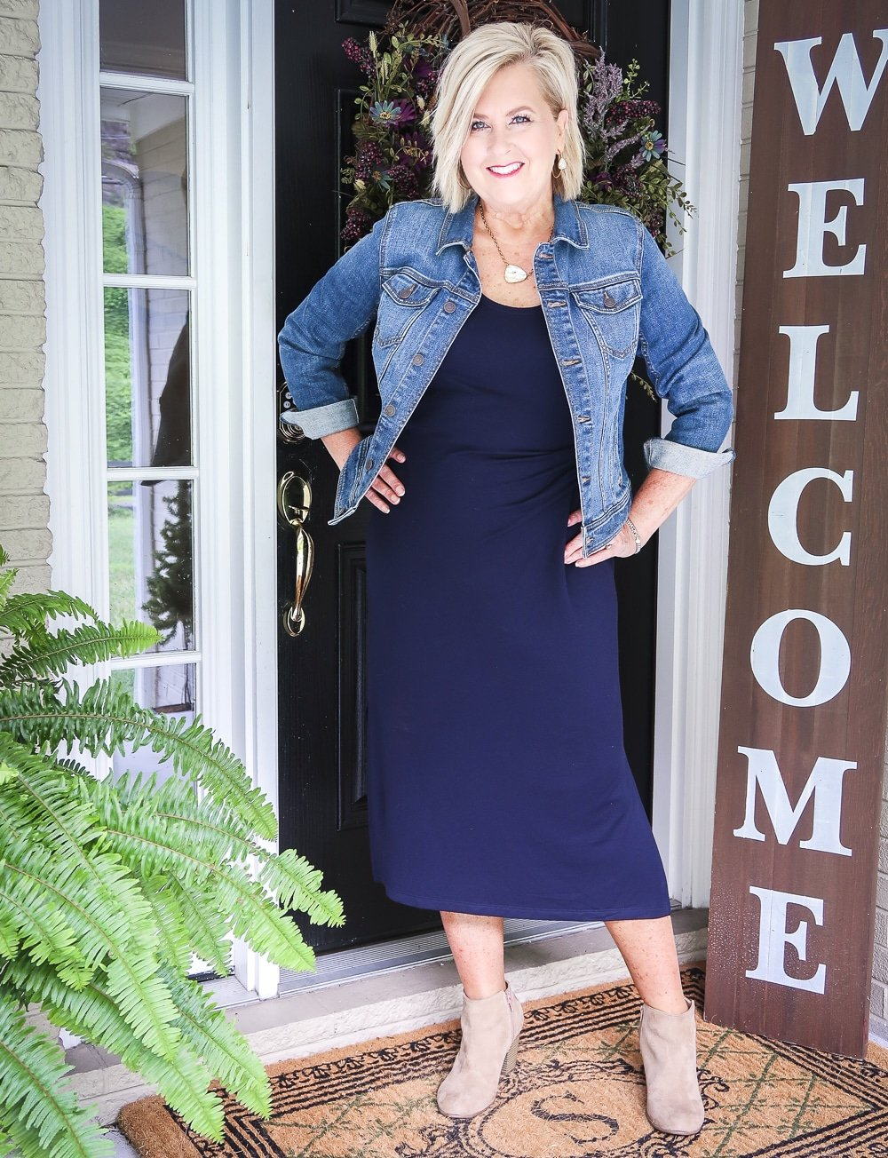 Fashion Blogger 50 Is Not Old is wearing a navy midi dress with a denim jacket and ankle booties from Old Navy