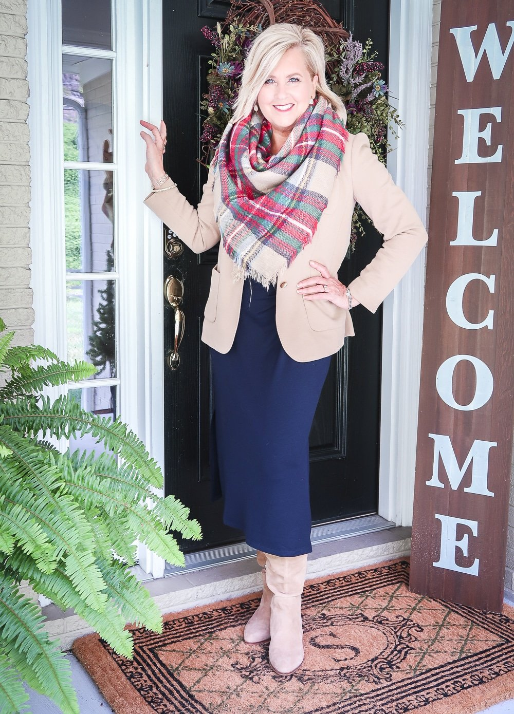 Fashion Blogger 50 Is Not Old is wearing a navy midi dress in all of the seasons. In winter, she added a tan blazer, a blanket scarf, and knee boots