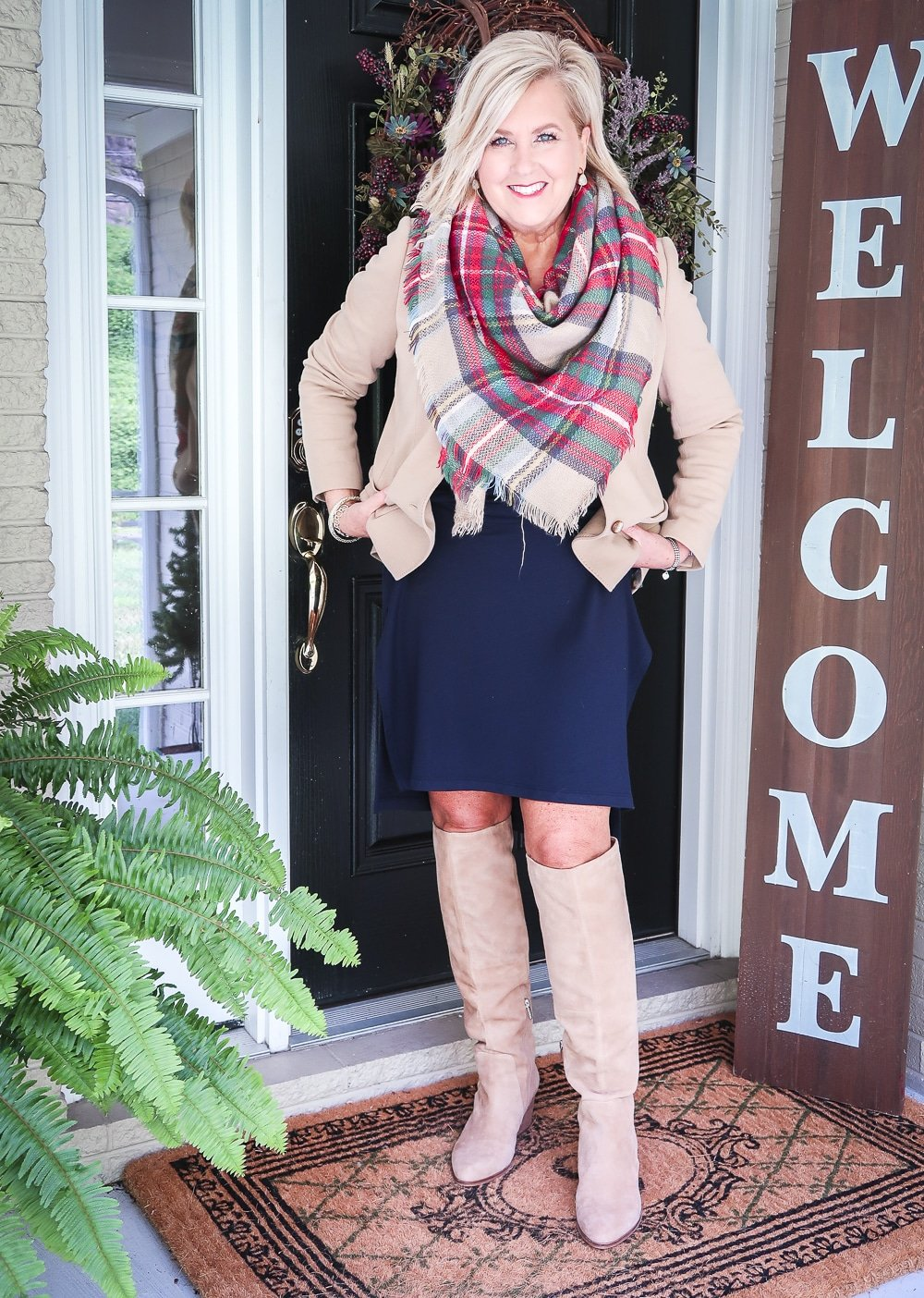 Fashion Blogger 50 Is Not Old is wearing a navy midi dress a tan blazer, a blanket scarf, and tan knee boots