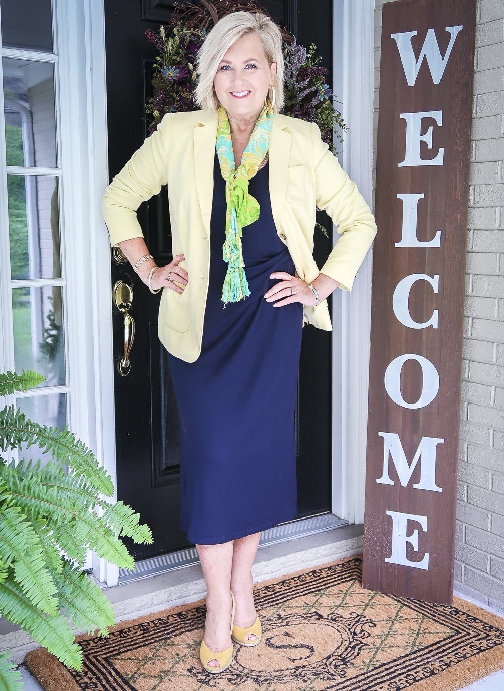Fashion Blogger 50 Is Not Old is wearing a navy midi dress in all of the seasons. In the spring of the year, she added a pale lemon yellow blazer, a bright scarf, and a pair of yellow espadrille wedge shoes