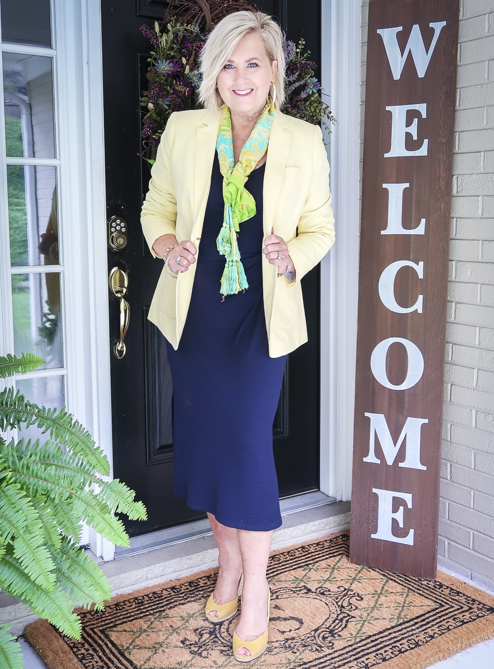 Fashion Blogger 50 Is Not Old is wearing a navy midi dress with a pale lemon yellow blazer, a bright scarf, and a pair of yellow espadrille wedge shoes