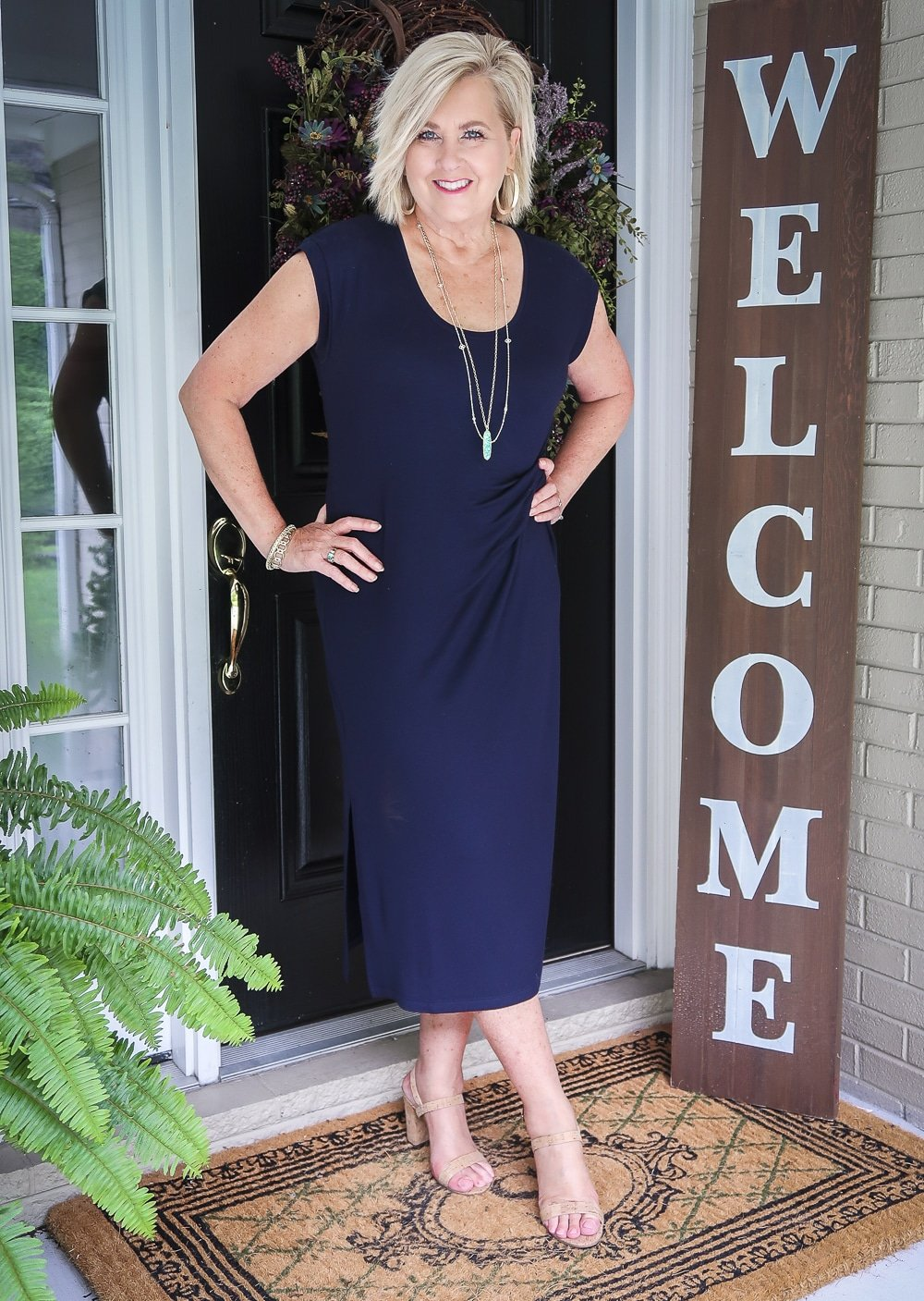 Fashion Blogger 50 Is Not Old is wearing a navy scoop neck midi dress with gold jewelry and cork heels
