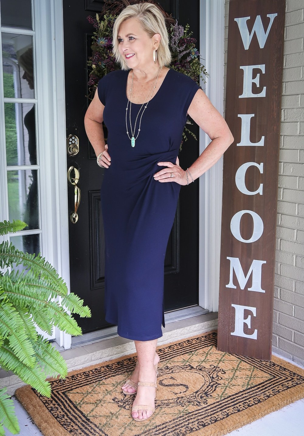 Fashion Blogger 50 Is Not Old is looking away and wearing a navy scoop neck midi dress with cork heels