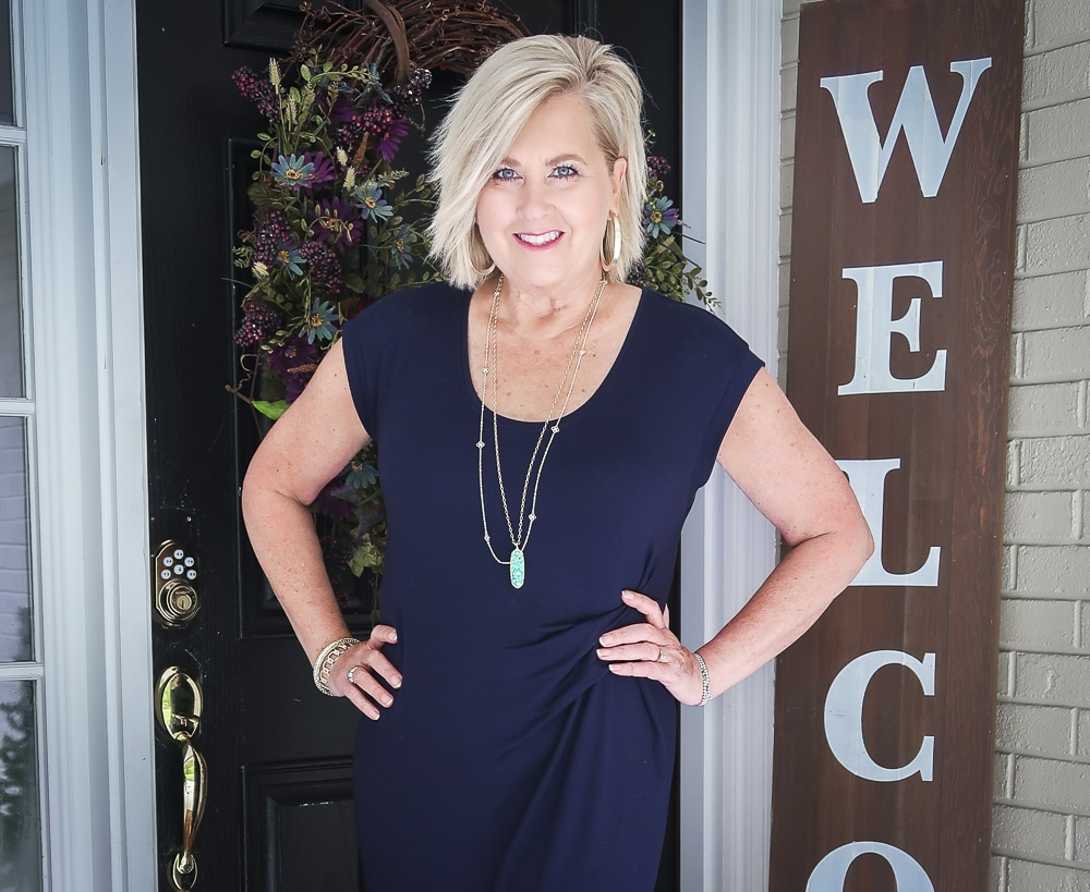 Fashion Blogger 50 Is Not Old is wearing a navy scoop neck midi dress with gold jewelry by Kendra Scott