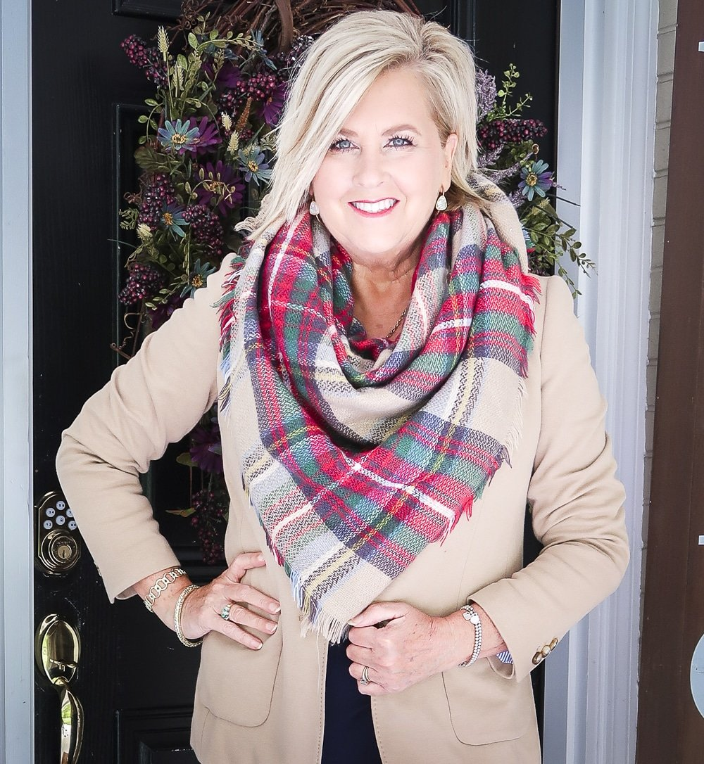 Fashion Blogger 50 Is Not Old is wearing a navy midi dress in all of the seasons. In winter, she added a tan blazer and a blanket scarf