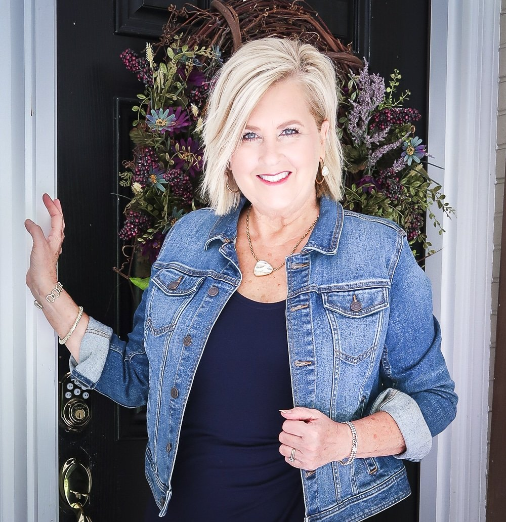 Fashion Blogger 50 Is Not Old is wearing a navy midi dress in all of the seasons. In the fall of the year, she added a denim jacket and gold jewelry from Kendra Scott
