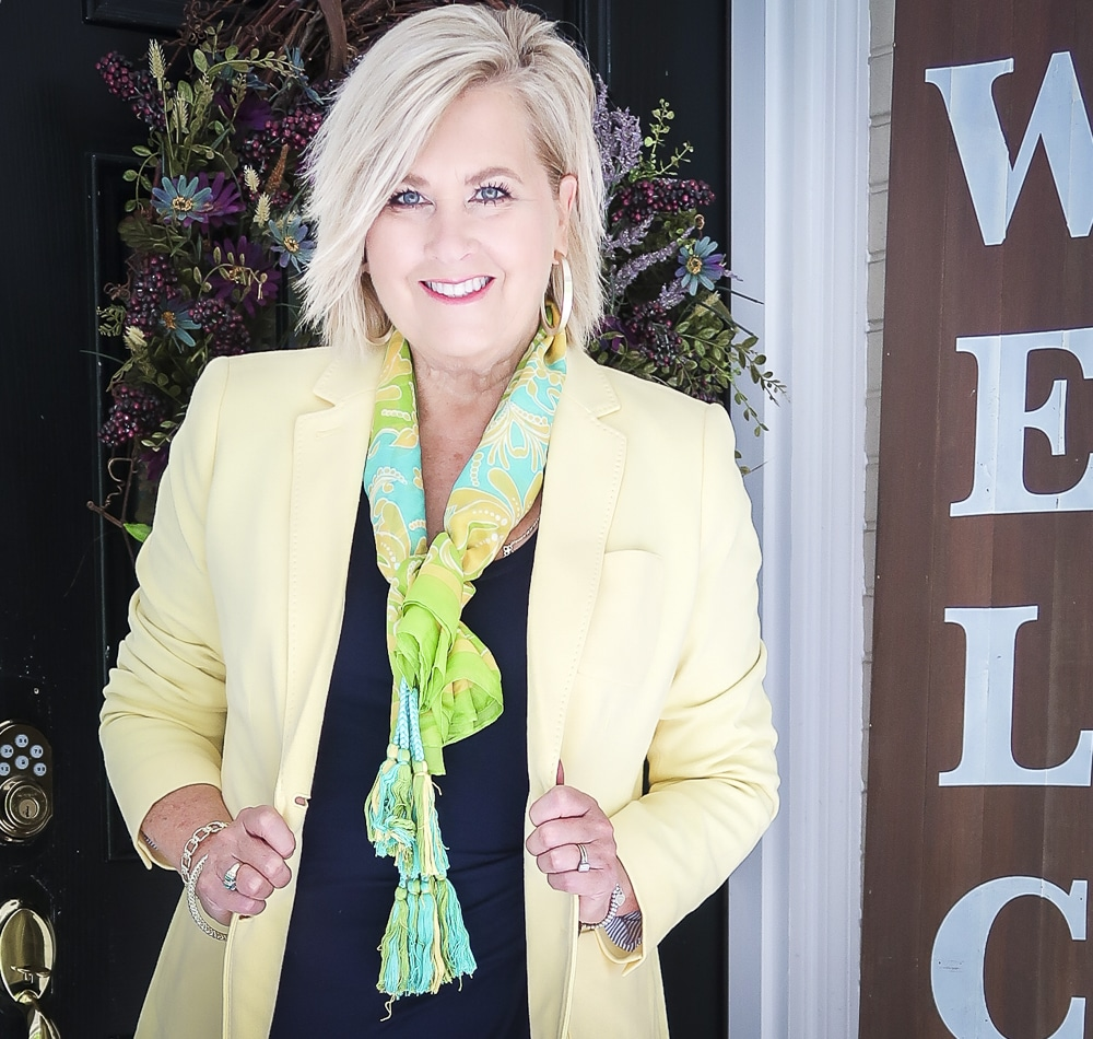 Fashion Blogger 50 Is Not Old is wearing a navy midi dress in all of the seasons. In the spring of the year, she added a pale lemon yellow blazer and a bright scarf