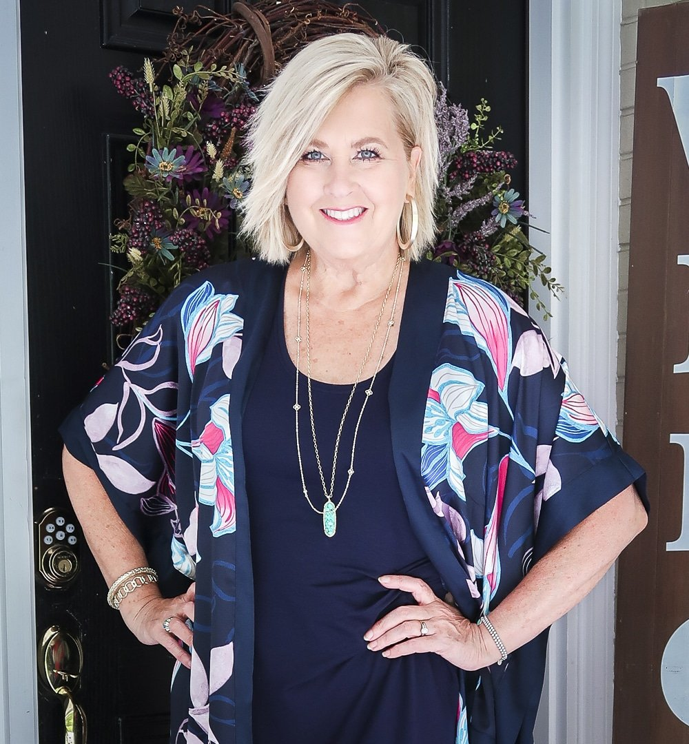 Fashion Blogger 50 Is Not Old is wearing a navy midi dress in all of the seasons. In summer, she added a floral kimono