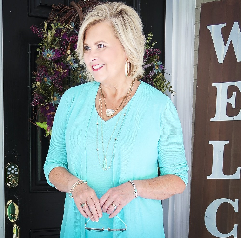 Fashion Blogger 50 Is Not Old is wearing a matching sweater set in Aqua, gold jewelry from Kendra Scott and looking to the side