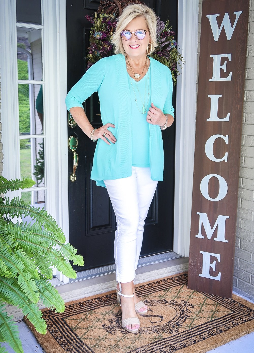 Fashion Blogger 50 Is Not Old is wearing glasses and a matching sweater set in Aqua, white crop pants, gold jewelry from Kendra Scott, and white espadrilles