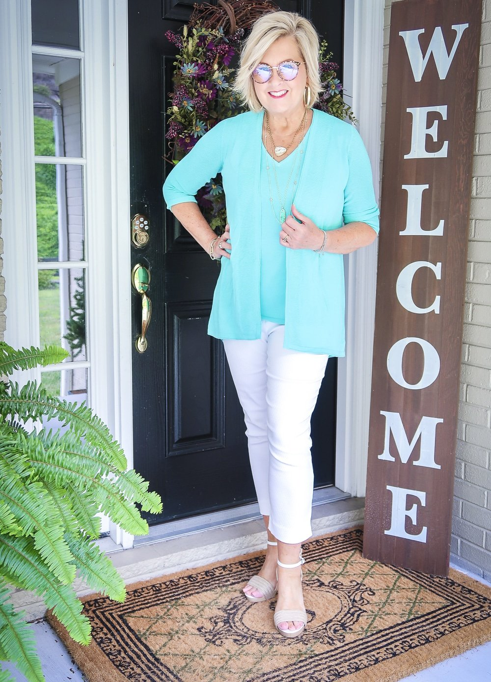 Fashion Blogger 50 Is Not Old is wearing a matching sweater set in Aqua, white crop pants, gold jewelry from Kendra Scott