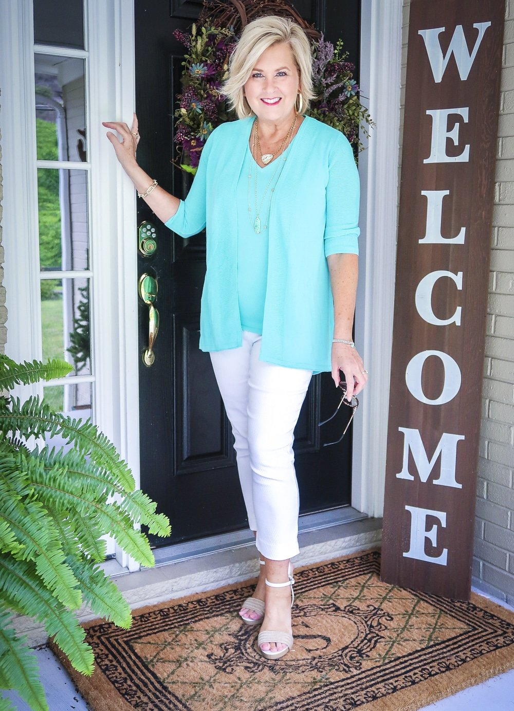 Fashion Blogger 50 Is Not Old is standing in front of a black door and wearing a matching sweater set in Aqua, white crop pants, gold jewelry from Kendra Scott, and white espadrilles