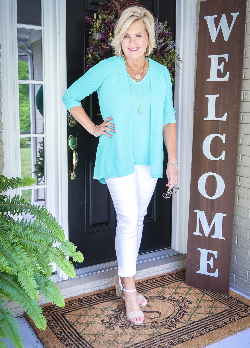 Fashion Blogger 50 Is Not Old is holding a pair of glasses and wearing a matching sweater set in Aqua, white crop pants, gold jewelry from Kendra Scott, and white espadrilles