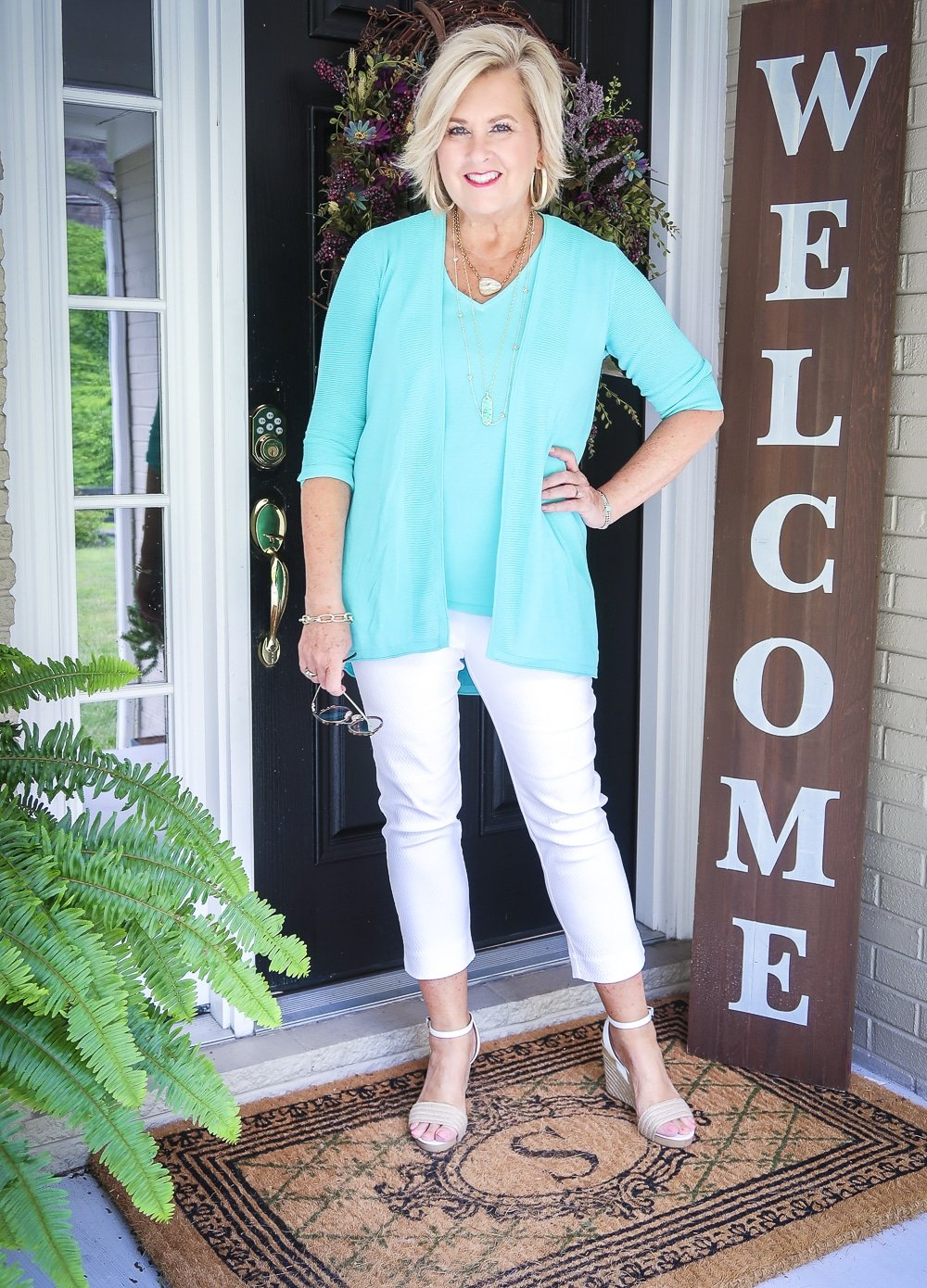 Fashion Blogger 50 Is Not Old is wearing a matching sweater set in Aqua, white crop pants, gold jewelry from Kendra Scott, and white espadrilles