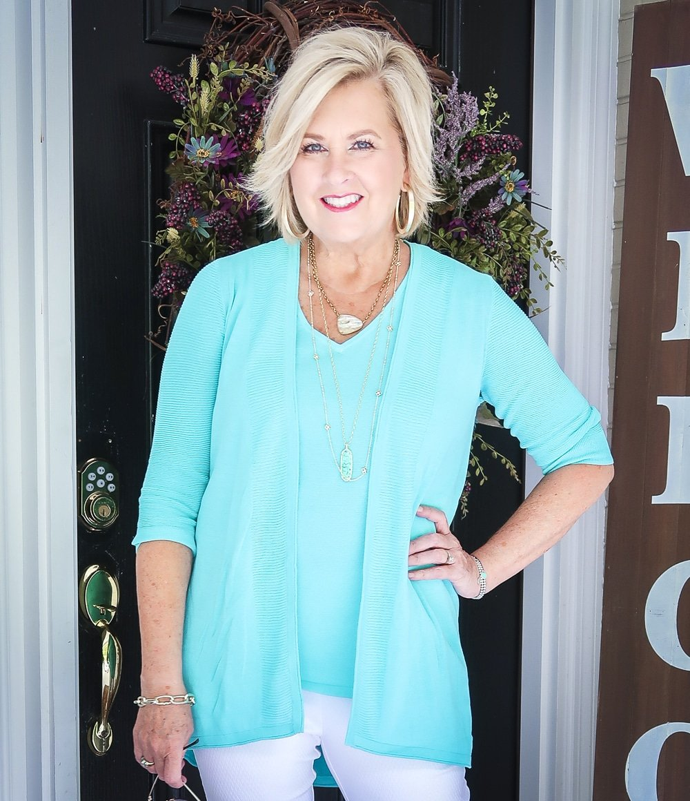 Fashion Blogger 50 Is Not Old is wearing a matching sweater set in Aqua from Chicos, and gold jewelry from Kendra Scott