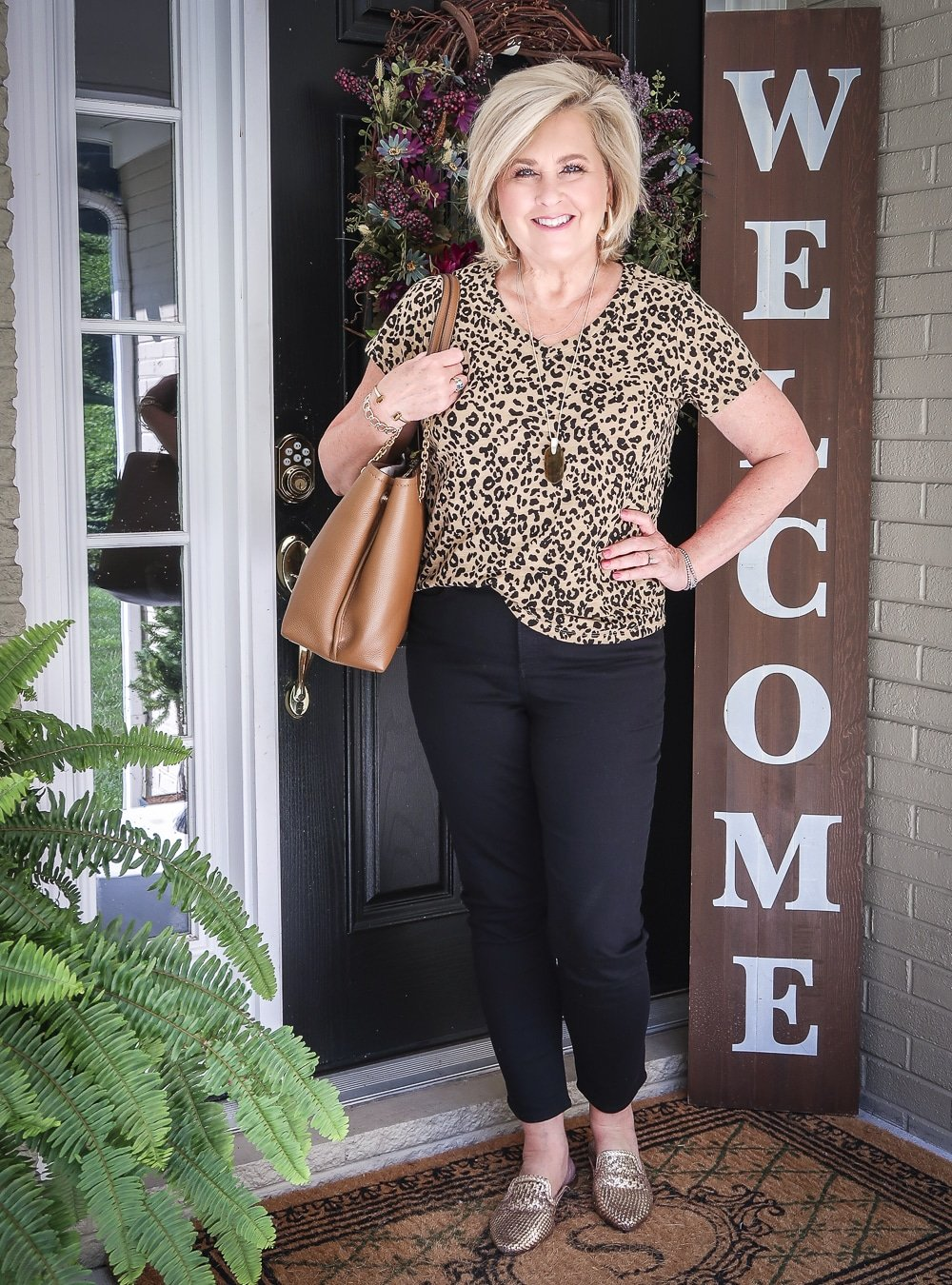 Fashion Blogger 50 Is Not Old is wearing a v-neck leopard tee, black girlfriend jeans, gold mules, and carrying a brown Tory Burch tote