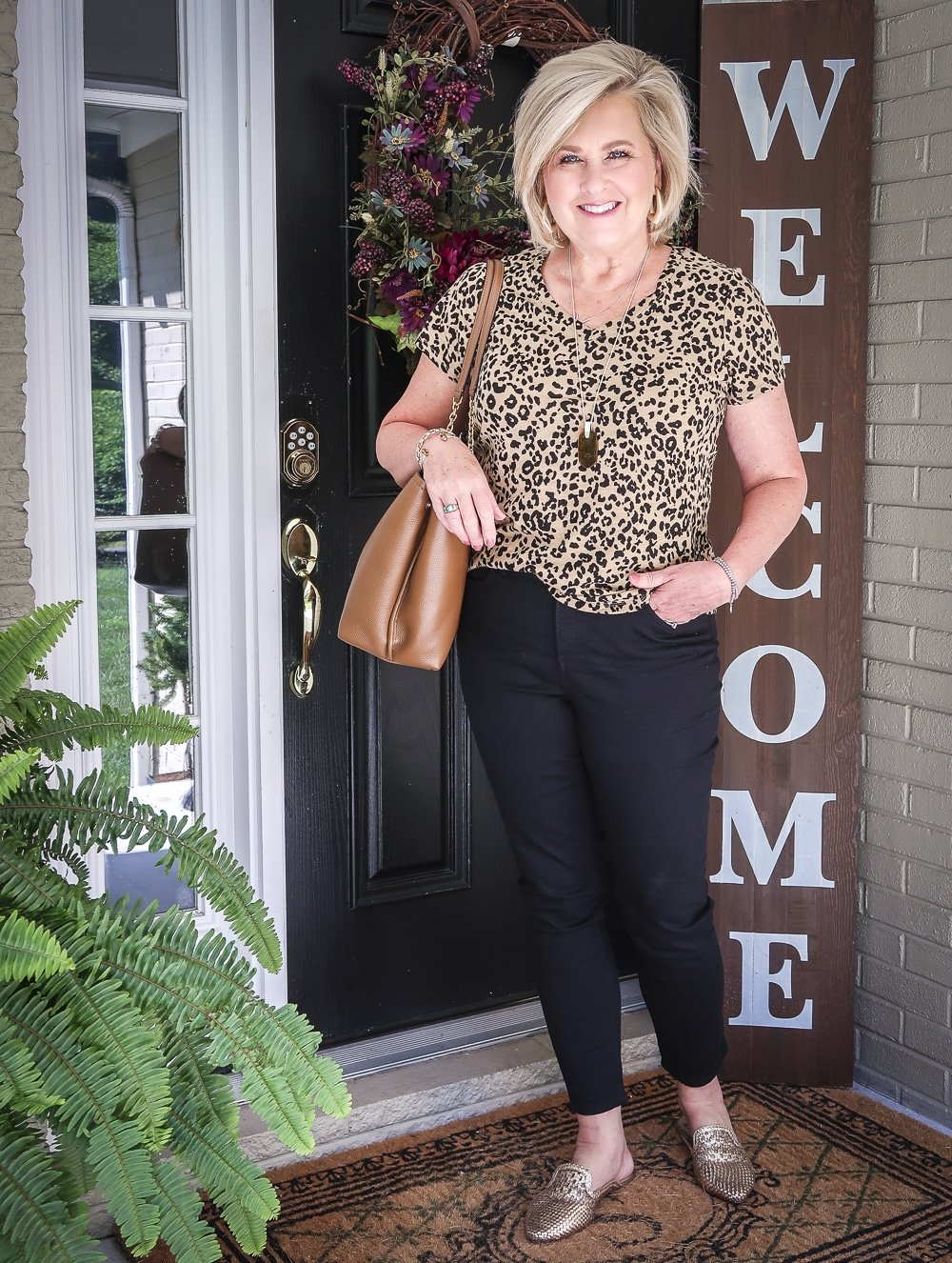 Fashion Blogger 50 Is Not Old is wearing a v-neck leopard tee, black girlfriend jeans, gold mules, and carrying a brown tote