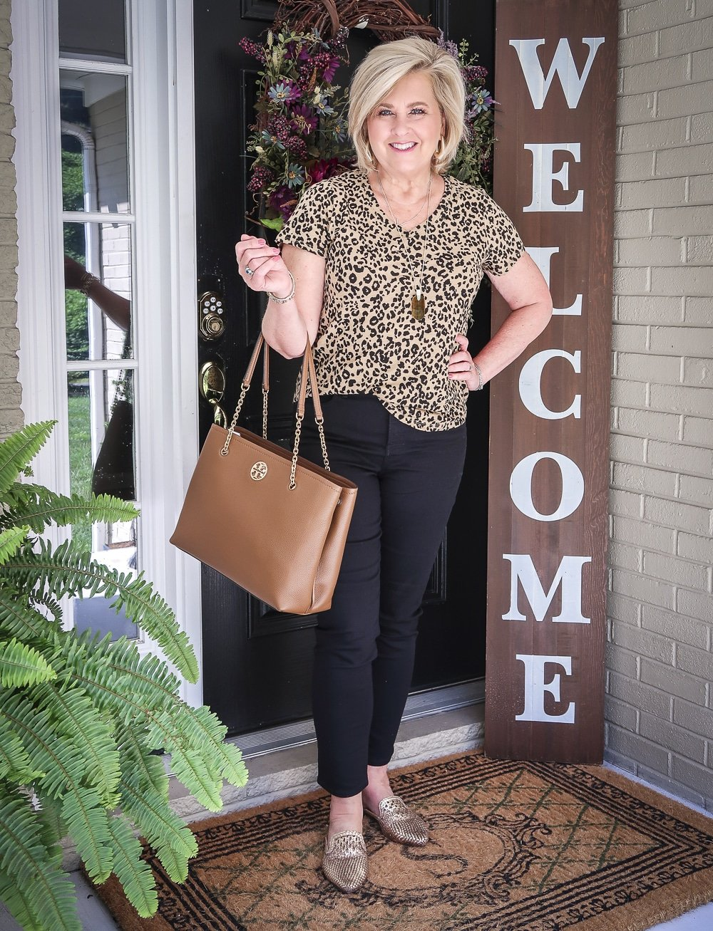 Fashion Blogger 50 Is Not Old is wearing a v-neck leopard tee, black jeans, gold mules, and carrying a brown Tory Burch tote