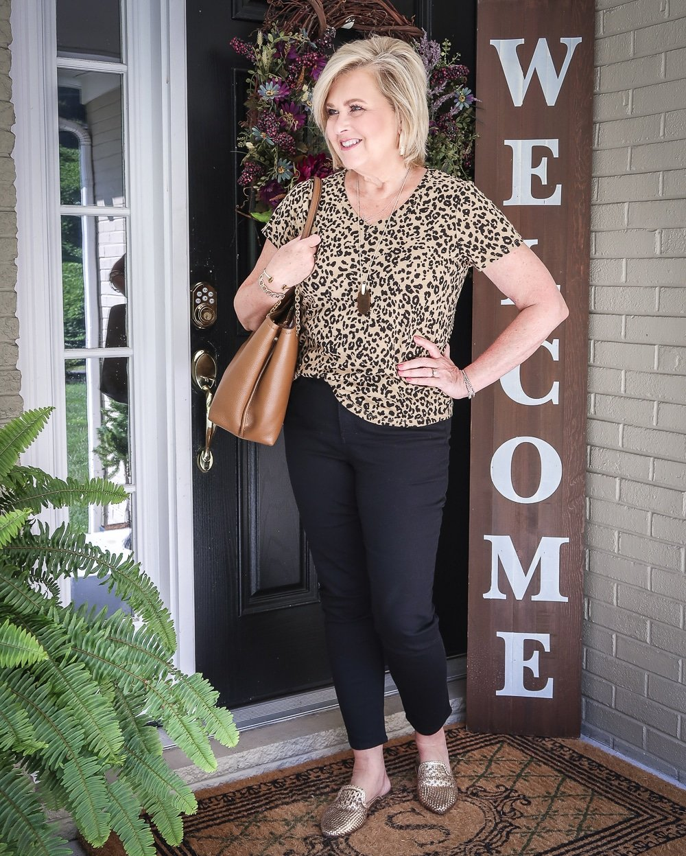 Fashion Blogger 50 Is Not Old is looking away and wearing a v-neck leopard tee, black girlfriend jeans, gold mules, and carrying a brown Tory Burch tote