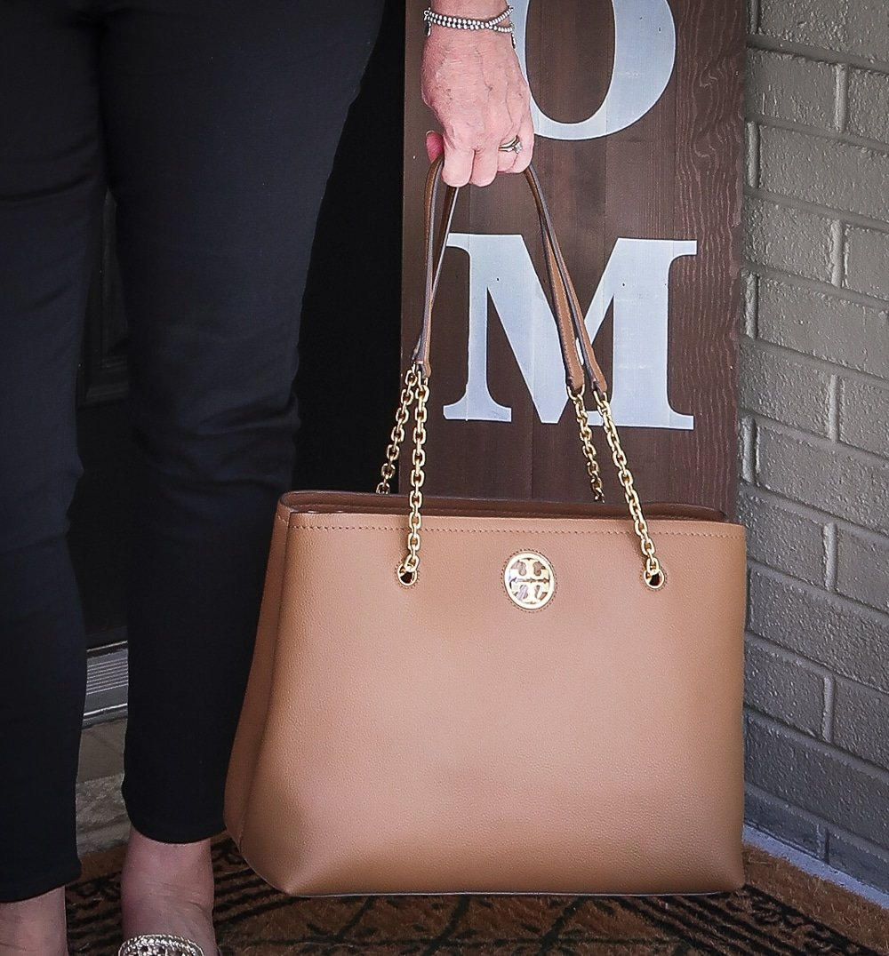 Fashion Blogger 50 Is Not Old is carrying a brown Tory Burch tote