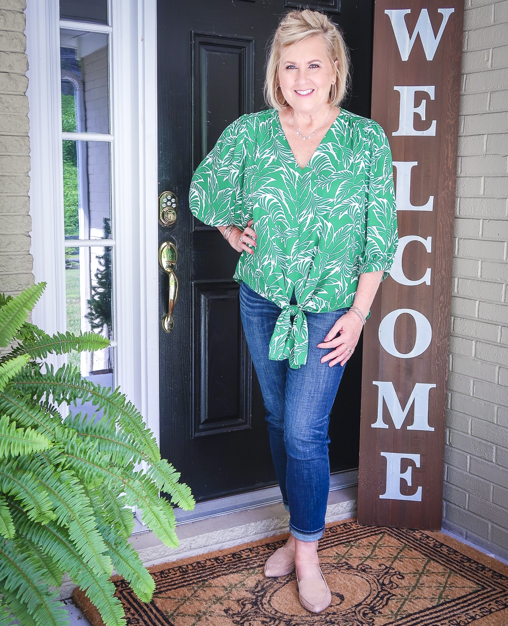 Fashion Blogger 50 Is Not Old is wearing a green palm print top and dark indigo girlfriend jeans with camel loafers