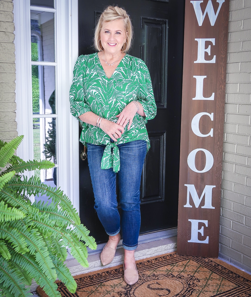 Fashion Blogger 50 Is Not Old is leaning against a door and wearing a green palm print blouse and dark indigo girlfriend jeans with camel loafers
