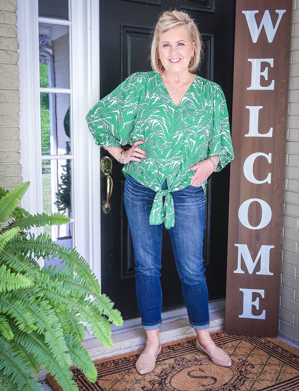 Fashion Blogger 50 Is Not Old has her hand in her pocket and is wearing a green palm print blouse and dark indigo girlfriend jeans with camel loafers