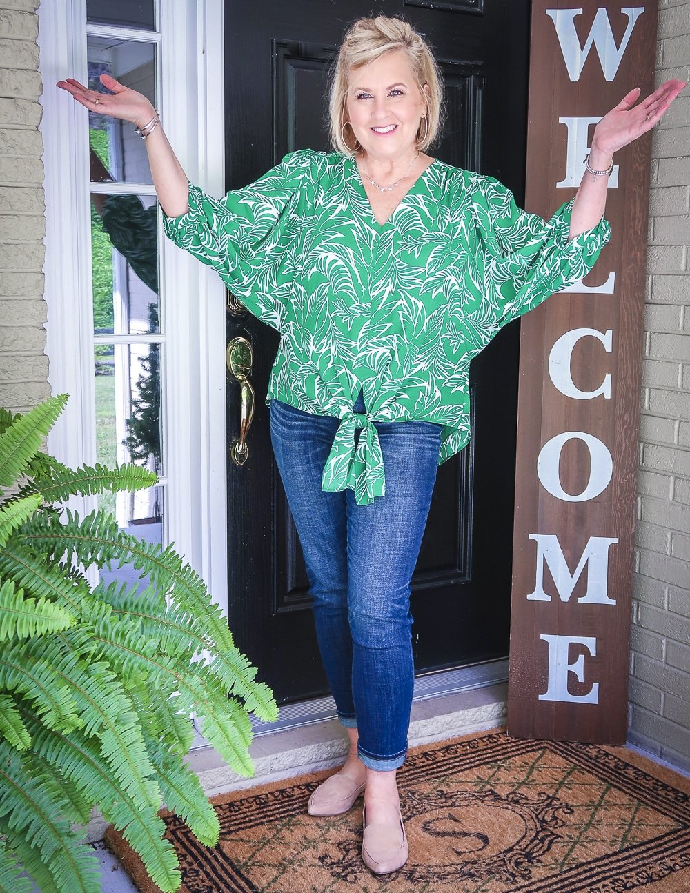 Fashion Blogger 50 Is Not Old is holding up her hands while wearing a green palm print blouse and dark indigo girlfriend jeans with camel loafers