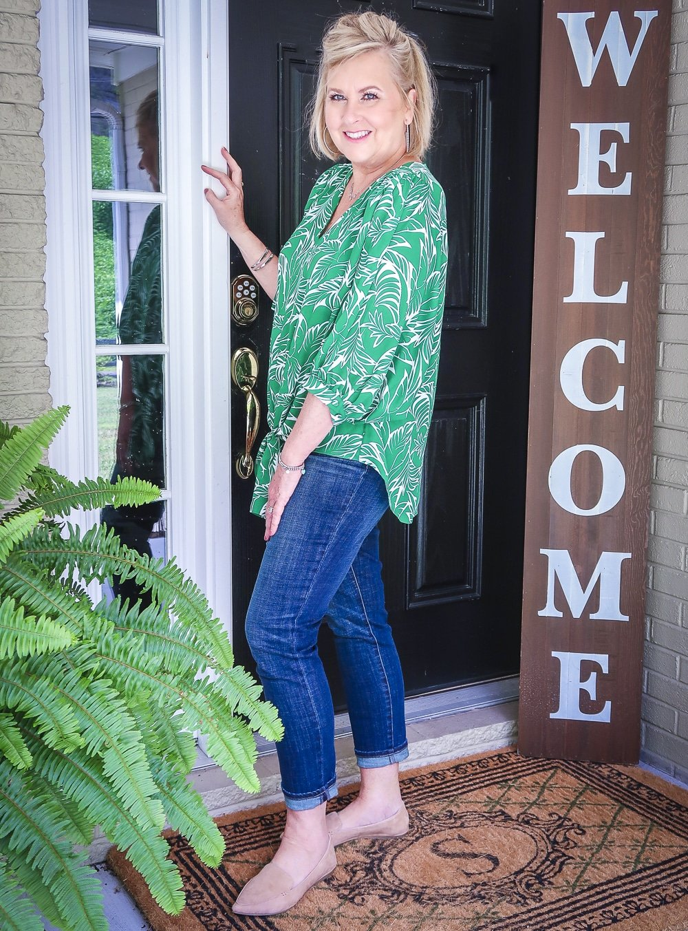 Fashion Blogger 50 Is Not Old is showing the side view of a green palm print blouse and dark indigo girlfriend jeans with camel loafers