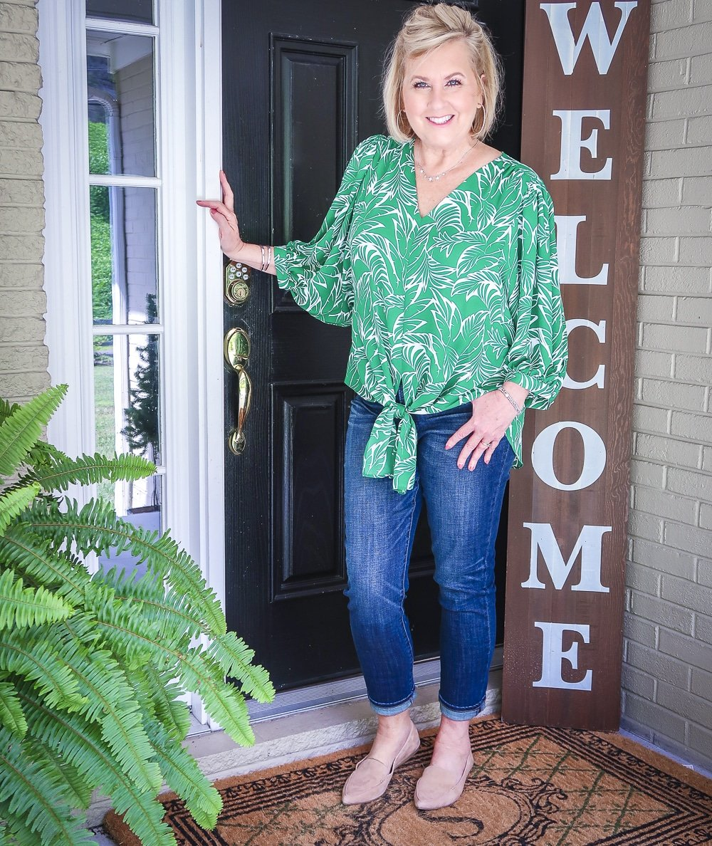 Fashion Blogger 50 Is Not Old is wearing a green palm print blouse and dark indigo girlfriend jeans with camel loafers